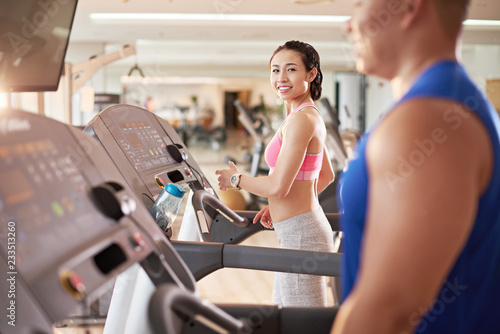 Poster Fitness Pretty smiling Asian woman looking at handsome man on threadmill next to her