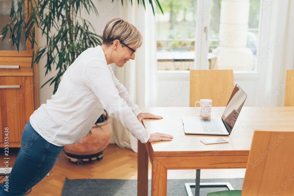 Fototapeta Woman doing exercises in her office
