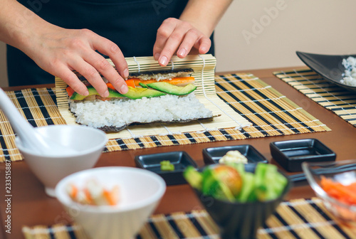 Poster Sushi bar Detail of hands of woman chef rolling up japanese sushi with rice, avocado and prawns on nori seaweed sheet