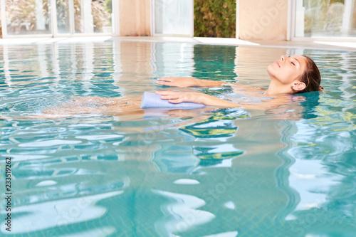 Valokuvatapetti Junge Frau im Pool macht Wasseryoga