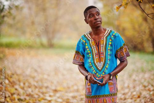 Fotografía  African man in africa traditional shirt on autumn park.