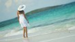 Ethnic Hispanic female in white dress on vacation ocean beach