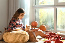 Woman With Cute Cat Resting At Home On Autumn Day