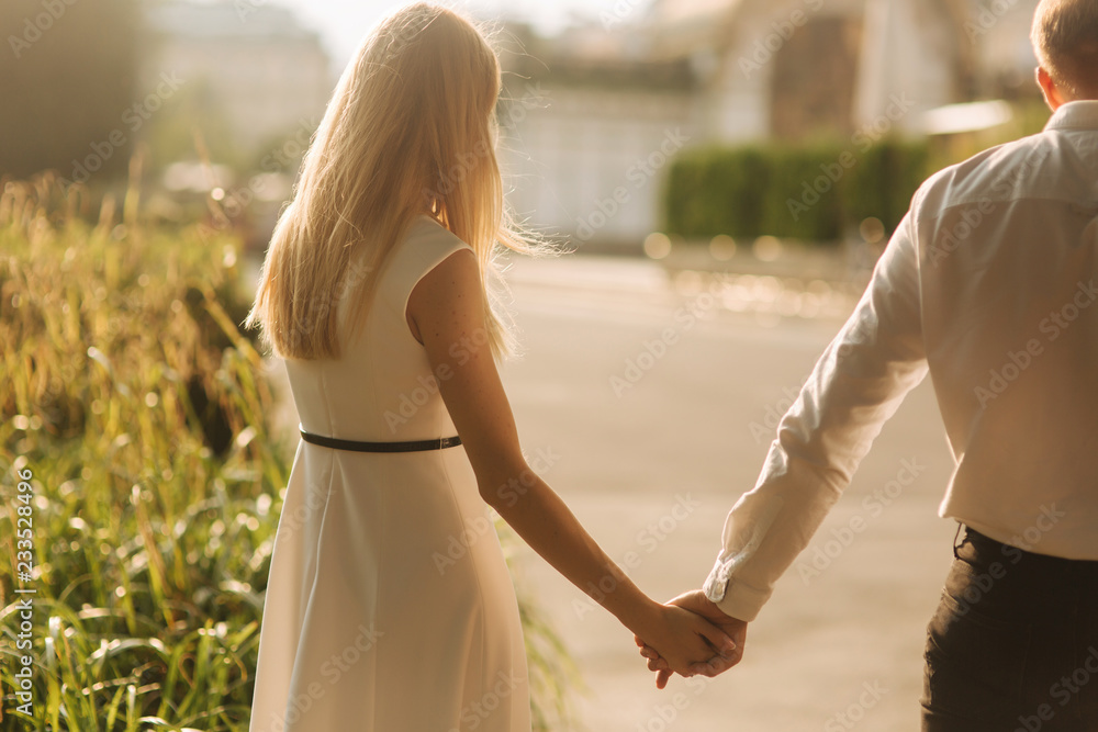 Fototapety, obrazy: Young beautiful couple husband in a white shirt and a woman in a dress walking around the park in summer time