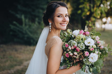 A Beautiful Bride Stands On Nature In Greenery With A Large Bouquet. Wedding Portrait Close-up Of The Young Bride. Wedding Photography.