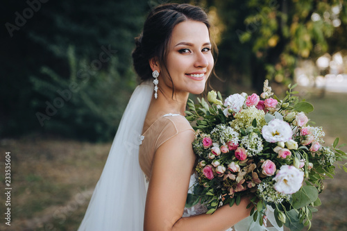 Foto A beautiful bride stands on nature in greenery with a large bouquet