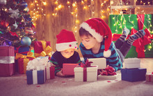 Two Brothers In Santa Hats Lying On The Floor