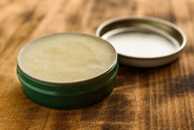 Organic Balm In Open Small Metal Can, Lid To The Side.