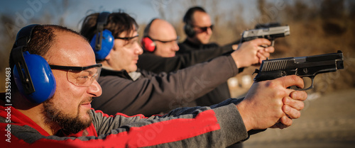 Fotomural Group of people practice gun shooting on outdoor shooting range