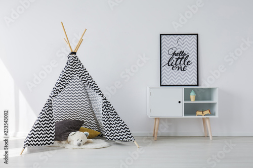 Patterned black and white scandinavian tent with grey and yellow pillows and white teddy bear next to wooden cabinet with poster in black frame, copy space on empty white wall