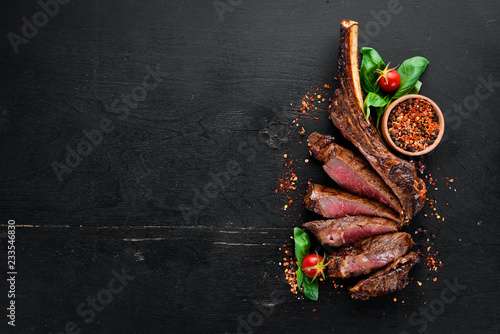 Photo Stands Steakhouse Steak on the bone. tomahawk steak On a black wooden background. Top view. Free copy space.