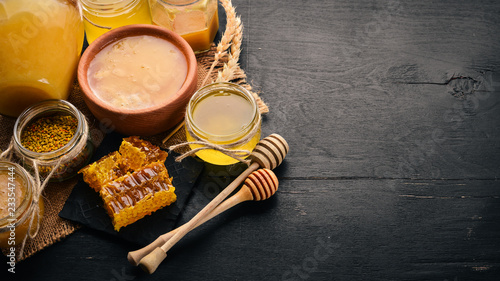 Fotobehang Bee A set of honey and bee products. Honey in honeycomb. On a black wooden background. Free space for text. Top view.