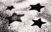 Print Of Stars On A Black Surface Dusted With Flour