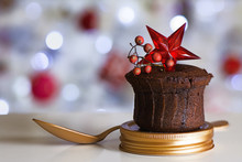 Chocolate Muffin With Red Star, Golden Spoon And Defocused Christmas Lights Background.