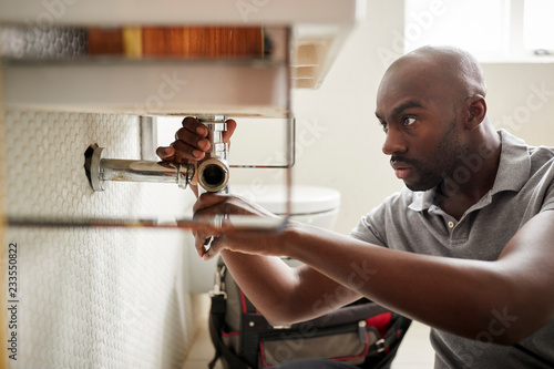 Young black male plumber sitting on the floor fixing a bathroom sink, close up