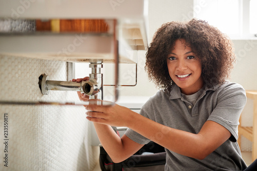 Young black female plumber sitting on the floor fixing a bathroom sink, looking to camera