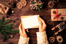 Female Hands Writing Letter To Santa Claus On Wooden Background With Christmas Gifts And Decoration Top View. Vintage Toned Image With Woman, Wish List For Christmas, Flat Lay, Copy Space, Background.