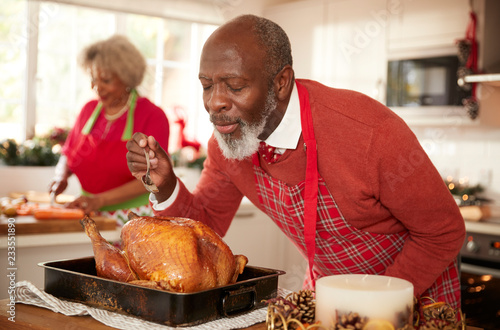 Senior black man basting roast turkey in preparation for Christmas dinner, his w Canvas Print
