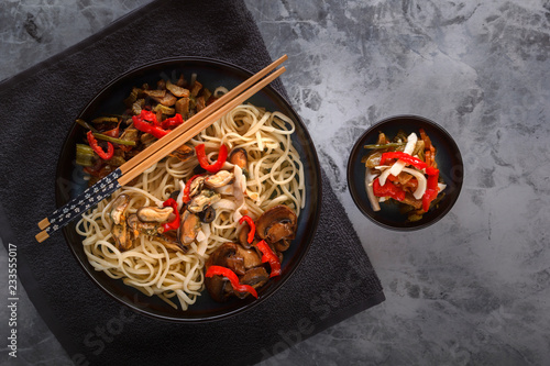 Traditional Asian food - noodles with seafood, salad, red pepper and fried mushrooms are on a gray table. Copy space. Top view