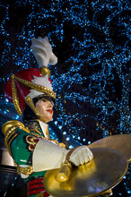 Scenic Night View Of Christmas Toy Soldier Decoration With Brass Cymbals In Front Of Sparkling Holiday Lights