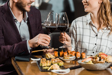 Partial View Of Couple Clinking And Having Date In Restaurant
