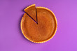 canvas print picture - Whole pumpkin pie with a cut slice. Above view. Purple background.