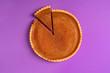Leinwandbild Motiv Whole pumpkin pie with a cut slice. Above view. Purple background.