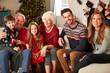 Leinwandbild Motiv Portrait Of Multi Generation Family Sitting On Sofa In Lounge At Home On Christmas Day