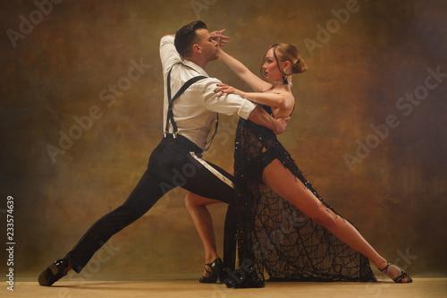Photo Flexible young modern couple dancing tango in studio
