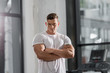 handsome muscular bodybuilder standing with crossed arms and looking at camera in gym