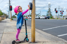 Young Girl In Pink Outfit And Pink Helmet Riding A Kick-scooter Pressing Button At Pedestriam Crossing