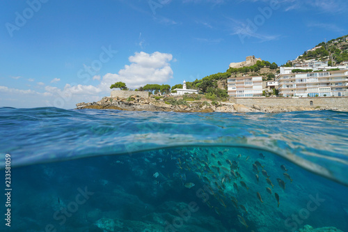 obraz PCV A lighthouse and buildings on a rocky coastline with a school of fish underwater, split view half above and below water surface, Spain, Costa Brava, Roses, Mediterranean sea, Catalonia