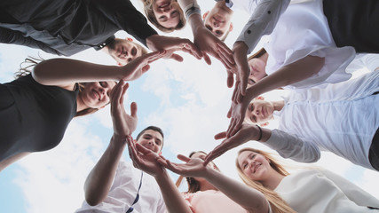 A group of high school students look through the shape of a circle created from their palms. The concept of friendly friends.
