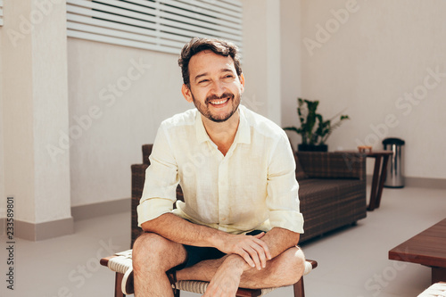 Photo Portrait of happy man sitting outdoors during sunny day