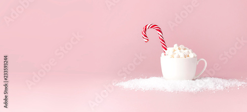 Spoed Foto op Canvas Dessert Christmas New Year drink, white mug with marshmallows and Candy Cane in the snow on pink background Flat Lay copy space. Winter traditional drink food. Festive decor, celebration Xmas holiday 2019