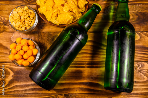 Tuinposter Bier / Cider Two bottles of beer and different snacks on wooden table. Top view