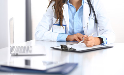 Unknown doctor woman filling up medical form while sitting at the desk in hospital office. Physician at work. Medicine and health care concept