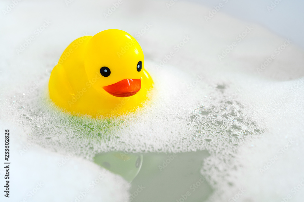 Fototapeta One yellow rubber duck with soap bubble bath, light  background with bubbles. Kids spa concept. Children`s bath time concept.