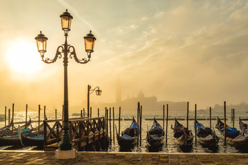 Panel Szklany Współczesny Gondolas in Venice at sunrise with Saint Giorgio island in morning fog, as seen from San Marco square