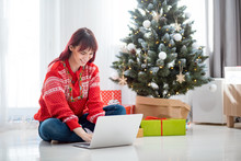 Young Woman Using Laptop Next To Xmas Tree, Christmas Shopping Online