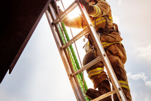 Low Angle View Of Firefighter Climbing Ladder Against Sky
