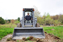 Farmer Driving Earth Mover In Farm