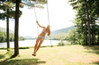 Happy woman hanging on rope at field