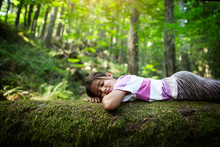 Girl Relaxing On Mossy Log In Forest