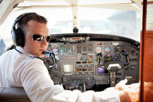 Portrait Of Pilot Sitting In Airplane