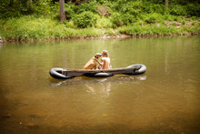 Man With Dog Sitting On Raft I...