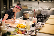Chef Writing At Table In Kitchen