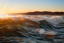 Waves Splashing Against Sky During Sunset