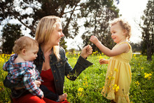 Cute Girl Giving Flower To Happy Mother Carrying Baby Boy At Field