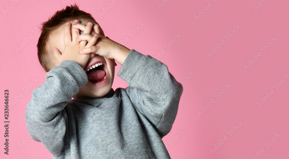 Fotografia Baby boy kid covering close his eyes with hands and palms screaming laughing  ov